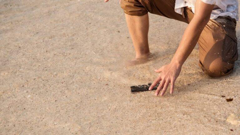 telefon upadł na piasek na plaży uszkodzony telefon